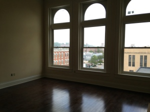 Large arched windows provide views of the Federal Courthouse in this Renwick apartment.
