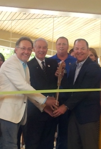 Mayor Bill Gluba assists Fidlar co-owners Dave Steil and Ernest Riggen with ribbon cutting duties.